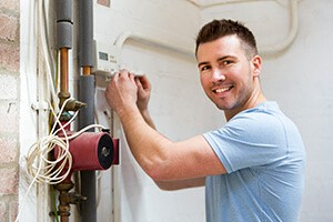 A young repairman is fixing a home heating system